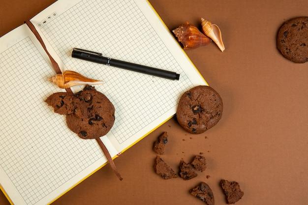 Вид сверху овсяного печенья с шоколадной стружкой и открытой пустой блокнот с ручкой на охре