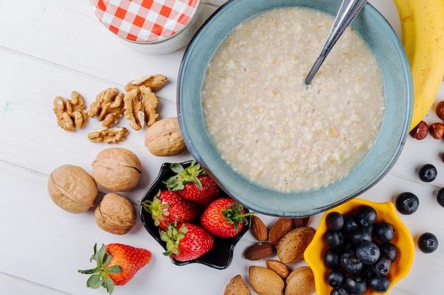木製の白い素朴なテーブルにボウルと新鮮な果実とナッツのオートミールのお粥の平面図