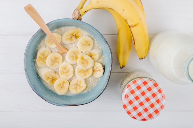素朴なテーブルのセラミックボウルにバナナとオートミールのお粥の平面図