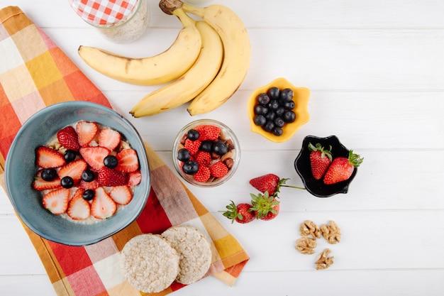 Вид сверху овсяной каши с ломтиками клубники черники в керамической миске и спелых бананов на столе