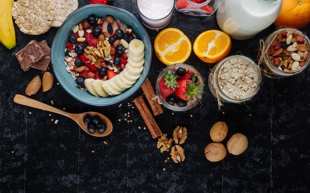 Вид сверху овсяной каши с клубникой, черникой, бананами, сухофруктами и орехами в керамической миске и стеклянных банках со смешанными орехами, овсяными хлопьями и овсяными хлопьями на столе.