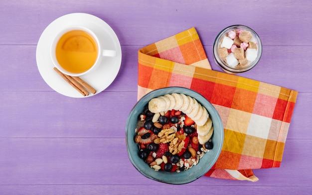 Вид сверху овсяной каши с клубникой, черникой, бананами, сухофруктами и орехами в керамической миске, сахарными кубиками в стеклянной банке и чашкой зеленого чая на фиолетовой деревянной поверхности