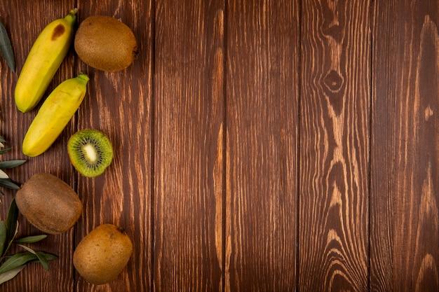 Взгляд сверху плодоовощей кивиа и банана изолированных на древесине с космосом экземпляра