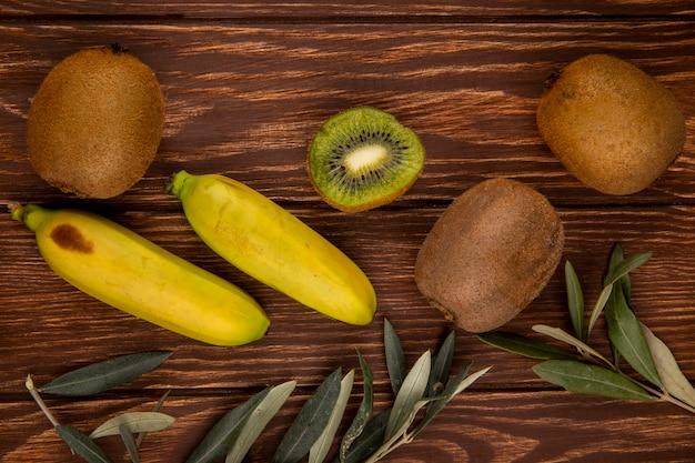 Взгляд сверху плодоовощей кивиа и банана изолированных на древесине