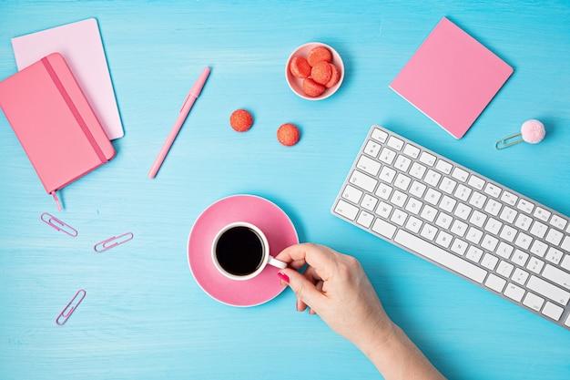 Вид сверху офисного стола. стол с клавиатурой, буфером обмена и канцелярскими принадлежностями розового цвета. плоская планировка домашнего офиса, удаленная работа, дистанционное обучение, видеоконференция, идея звонков