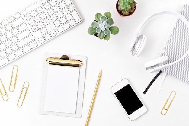 オフィスデスクの上面図。キーボード、スマートフォン、クリップボード、事務用品を備えたテーブル。フラットレイホームオフィスワークスペース、リモートワーク、遠隔教育、ビデオ会議、電話のアイデア