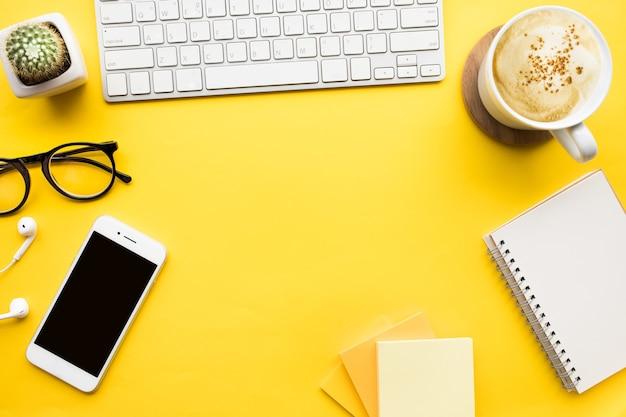 Вид сверху офисного стола стола с современными аксессуарами, расходными материалами на цветном фоне.