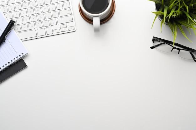 Вид сверху офисного стола с кофе, очками, клавиатурой, ноутбуком и копией пространства.