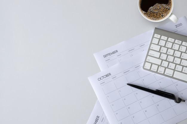 白いテーブルの上のコーヒーカップ、キーボード、作業スケジュールのオフィスデスクのトップビュー