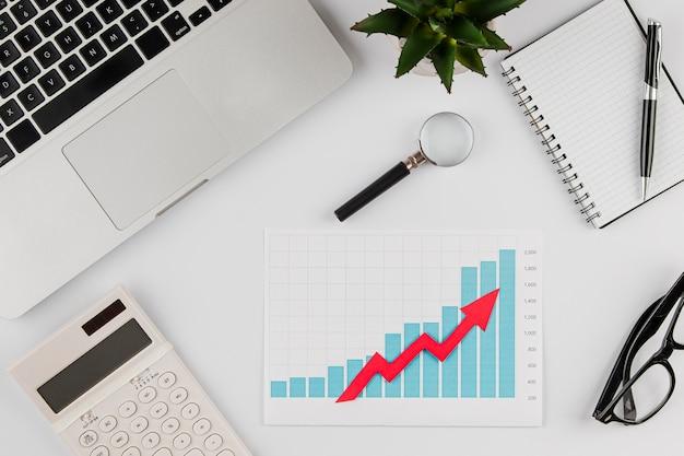 Вид сверху офисного стола с диаграммой роста и ноутбука