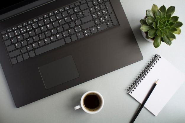 노트북, 커피 컵, 선인장과 사무실 책상의 최고 볼 수 있습니다. 작업 공간 책상의 평평한 누워.