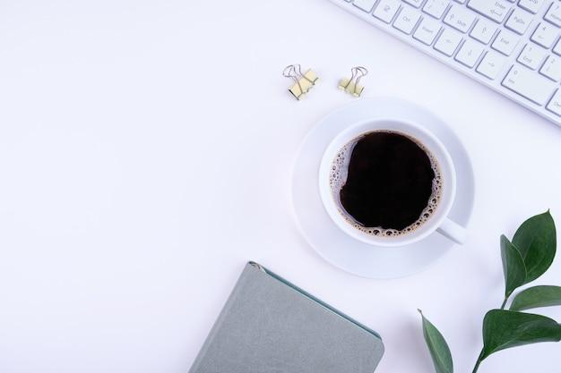 ノートパソコン、メモ帳、コーヒー、白い背景の上のコピースペースを持つ葉のオフィスデスクのトップビュー