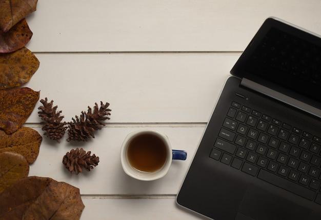 白いテーブルの背景のフラットレイにお茶とラップトップとオフィスデスクワークスペースの上面図
