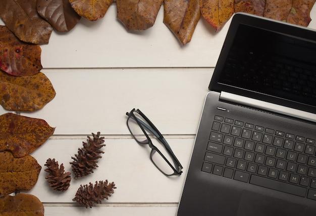 白いテーブルの背景にラップトップと眼鏡とオフィスデスクワークスペースの上面図。フラットレイ