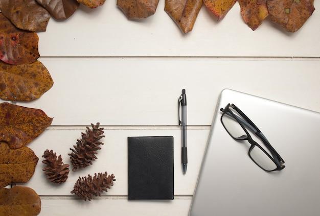 白いテーブルの背景にノートブックとラップトップとオフィスデスクワークスペースの上面図。フラットレイ