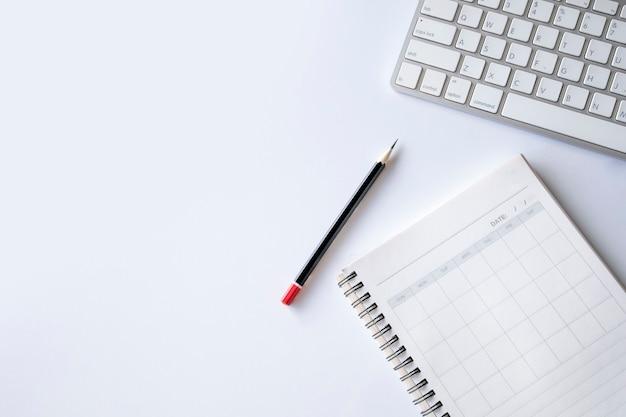 白いテーブルの背景に開いた本、鉛筆、キーボードとオフィスデスクワークスペースの上面図。フラットレイ