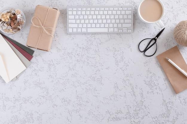 Взгляд сверху канцелярских принадлежностей и аксессуаров офиса, подарочных коробок, конверта и чашки кофе латте. минималистичная плоская планировка, винтажное рабочее место для домашнего офиса