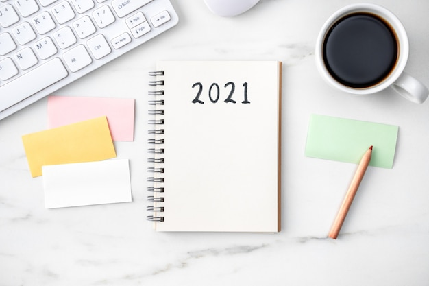 Вид сверху на офисный стол, концепция работы 2021 года с клавиатурой, блокнотом, карандашом, очками и кофе