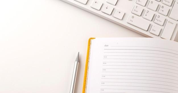 Вид сверху концепции стола офисного стола с клавиатурой, планированием ноутбука, карандашом на белом фоне.
