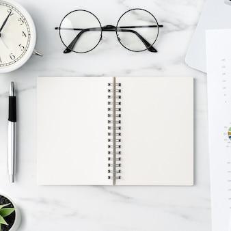 空白のノートブック、レポート、目覚まし時計とオフィステーブルデスクワークコンセプトの上面図