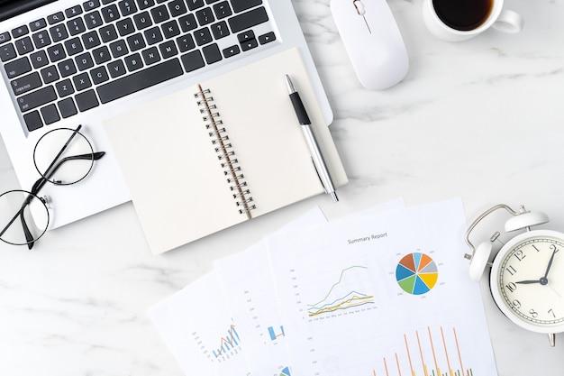 空白のノートブックとオフィステーブルワークコンセプトの上面図