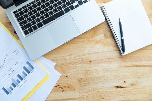 分析チャート、コンピュータラップトップ、白い空白のノートブックを備えたオフィスの木製デスクトップのトップビュー
