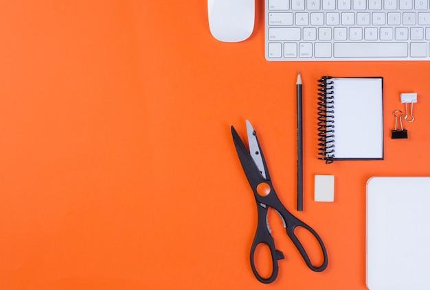 Вид сверху офисного рабочего места, оранжевого письменного стола с клавиатурой, карандашом, ножницами, мышью, записной книжкой и скрепками. с копией пространства, плоская планировка.