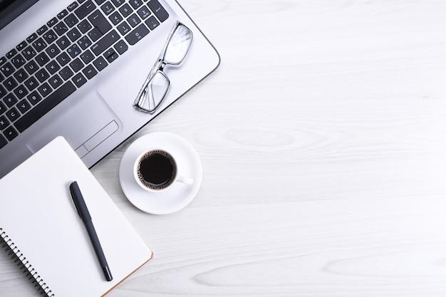 オフィスの作業スペース、ラップトップノートブック、キーボード、ペン、眼鏡、電話、ノートブック、コーヒーのカップが付いている木製の机のテーブルの上面図。コピースペース、フラットレイ。モックアップ。