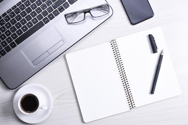 Вид сверху офисного рабочего места, деревянный стол с ноутбуком, клавиатура, ручка, очки, телефон, ноутбук и чашка кофе.