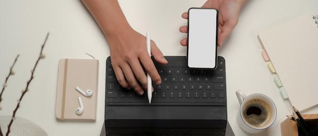 Вид сверху офисного работника, работающего с цифровым планшетом и смартфоном