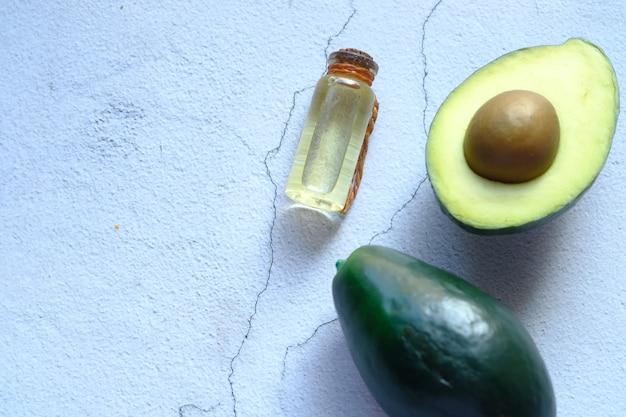 Вид сверху масла и ломтик авокадо на деревянном столе.