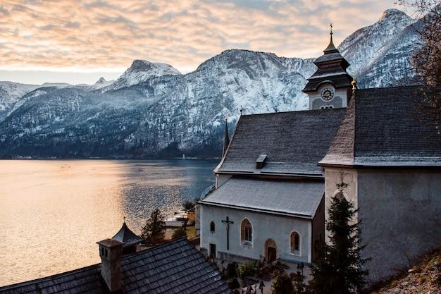 Вид сверху на старую церковь в гальштате с потрясающим видом на высокие снежные альпы на заднем плане