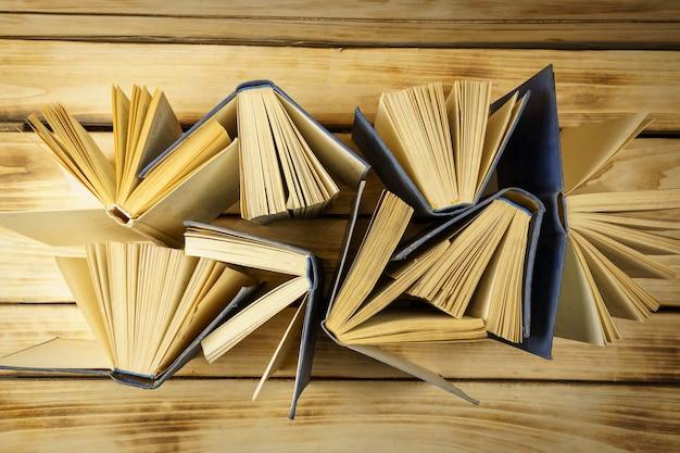 木の表面の古いハードカバーの本の上面図。本からの表面。開いた本、めくったページ。