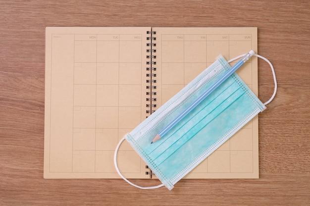 古いノートブック、アンチウイルスマスク、木製のテーブルの上の鉛筆の上面図。