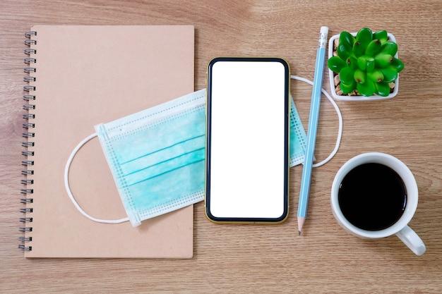 古いノートブック、アンチウイルスマスク、スマートフォン、木製テーブルの上のコーヒーカップの上面図