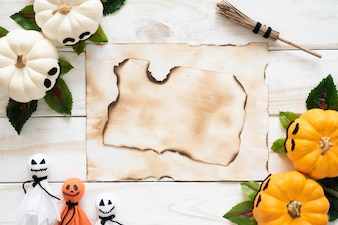 Top view of old paper with yellow ghost pumpkins on wooden board. halloween concept