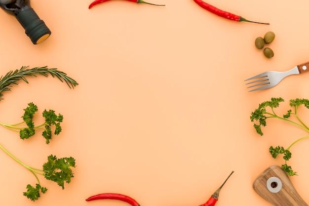 Вид сверху оливкового масла и перца со столовыми приборами