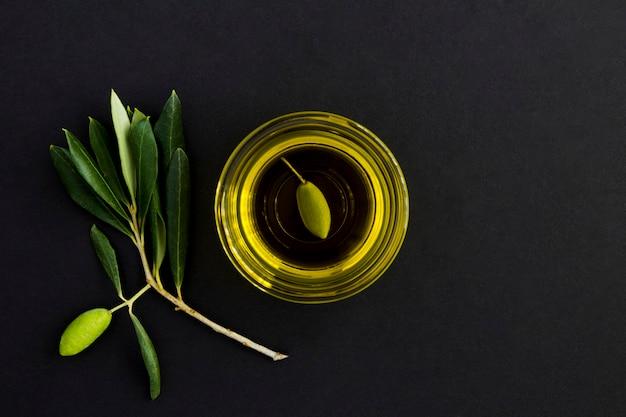 Вид сверху оливкового масла в стеклянной миске и ветке с зелеными оливками на черном фоне. скопируйте пространство.