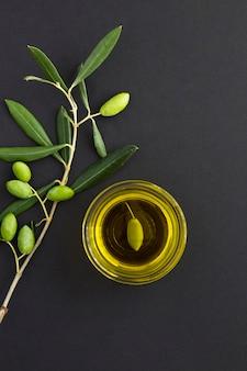 ガラスのボウルと黒の背景に緑のオリーブと枝のオリーブオイルの上面図。場所は垂直です。