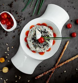 Вид сверху салат оливье, украшенный вареным яйцом, половиной помидоров черри и луком