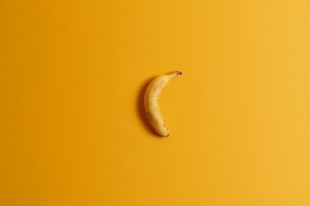 Вид сверху одного спелого банана, изолированного на желтом фоне. вкусные тропические фрукты для вкусного завтрака или закуски. готов съесть целый банан. полезный питательный продукт, богатый витаминами