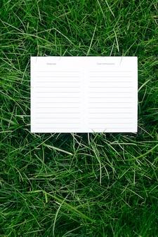 Вид сверху одной белой картонной пустой инструкции по уходу и макет материалов газонной зеленой травы с биркой для логотипа.