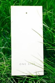 ロゴの芝生の緑の草のタグの碑文のワンサイズのレイアウトで1つの白い段ボールタグの上面図。