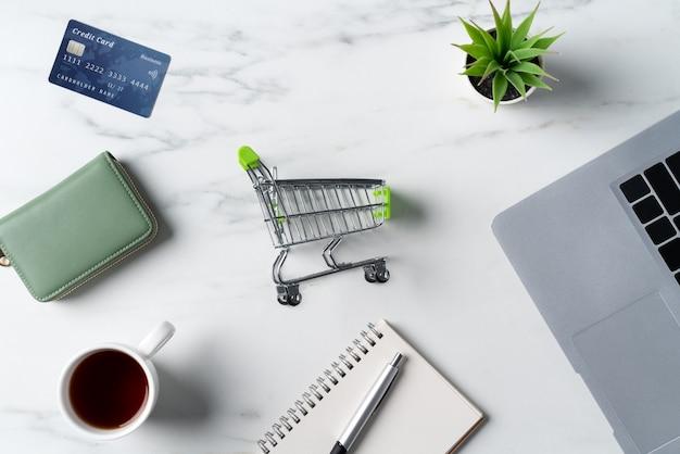 사무실 대리석 흰색 테이블 배경에 격리된 신용 카드와 노트북 컴퓨터를 사용한 온라인 쇼핑 개념의 상위 뷰.