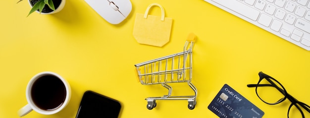 신용 카드, 스마트 폰 및 사무실 노란색 테이블 배경에 고립 된 컴퓨터와 온라인 쇼핑 개념의 최고 볼 수 있습니다.