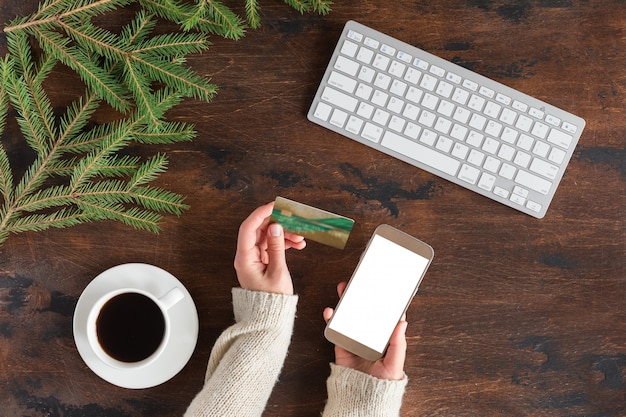 Вид сверху онлайн покупок, кредитной карты и смартфона с пустым экраном на руке женщины