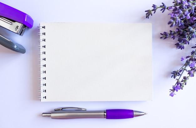 ラベンダーの花束と開いた空白のメモ帳の上面図、テキストのコピースペース