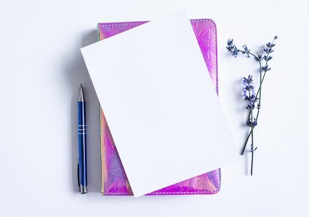 黒い石の背景にラベンダーの花束と開いている空白のメモ帳の上面図、テキストのコピースペース