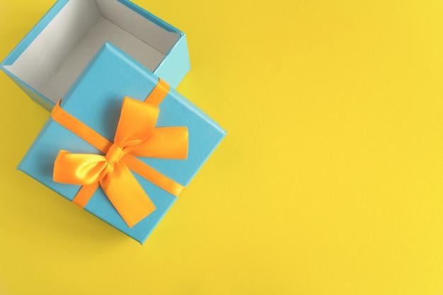 Вид сверху открытой синей подарочной коробки на желтом