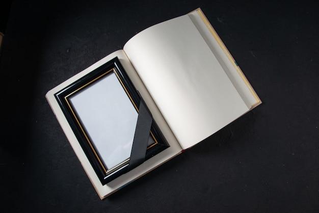 Вид сверху открытой книги с картинной рамкой на темной стене